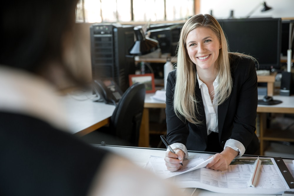 Young business woman smiling at client