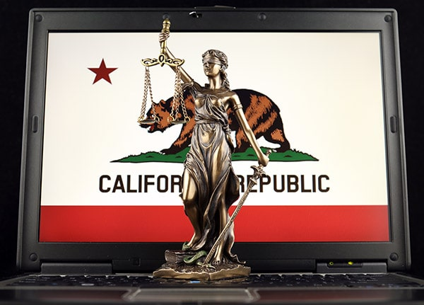Lady Justice standing in front of California flag on computer screen